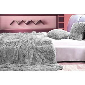 Deky jako chlupaté přehozy šedé barvy na postel