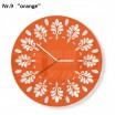 Oranžové nástěnné hodiny s ornamenty
